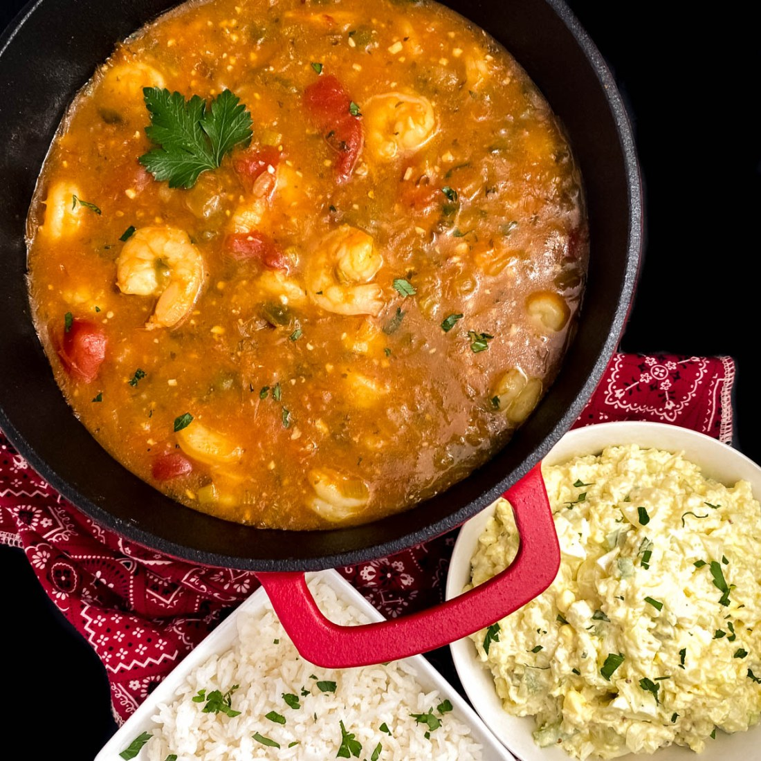 A red cast iron Dutch oven filled with gluten free keto Paleo Cajun shrimp etouffee with a red bandana and bowls of rice and cauliflower rice.