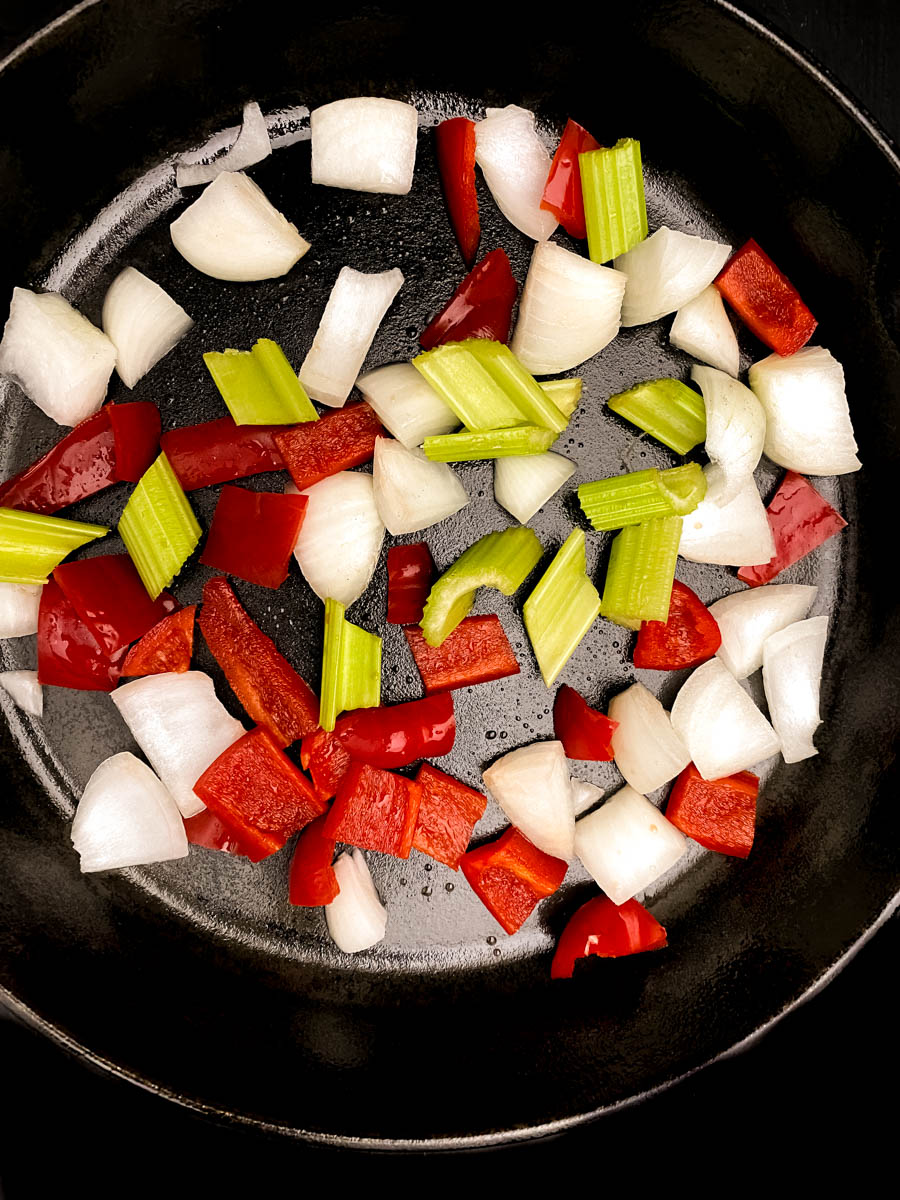 The Cajun trinity of onion, bell pepper, and celery in a black cast iron skillet.
