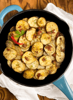 A blue cast iron skillet filled with Cayenne Cumin Rosemary Roasted Potatoes against a brown background.