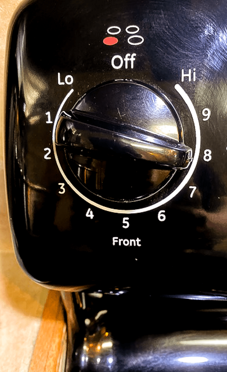 An electric stove dial set to number 8, or high heat.
