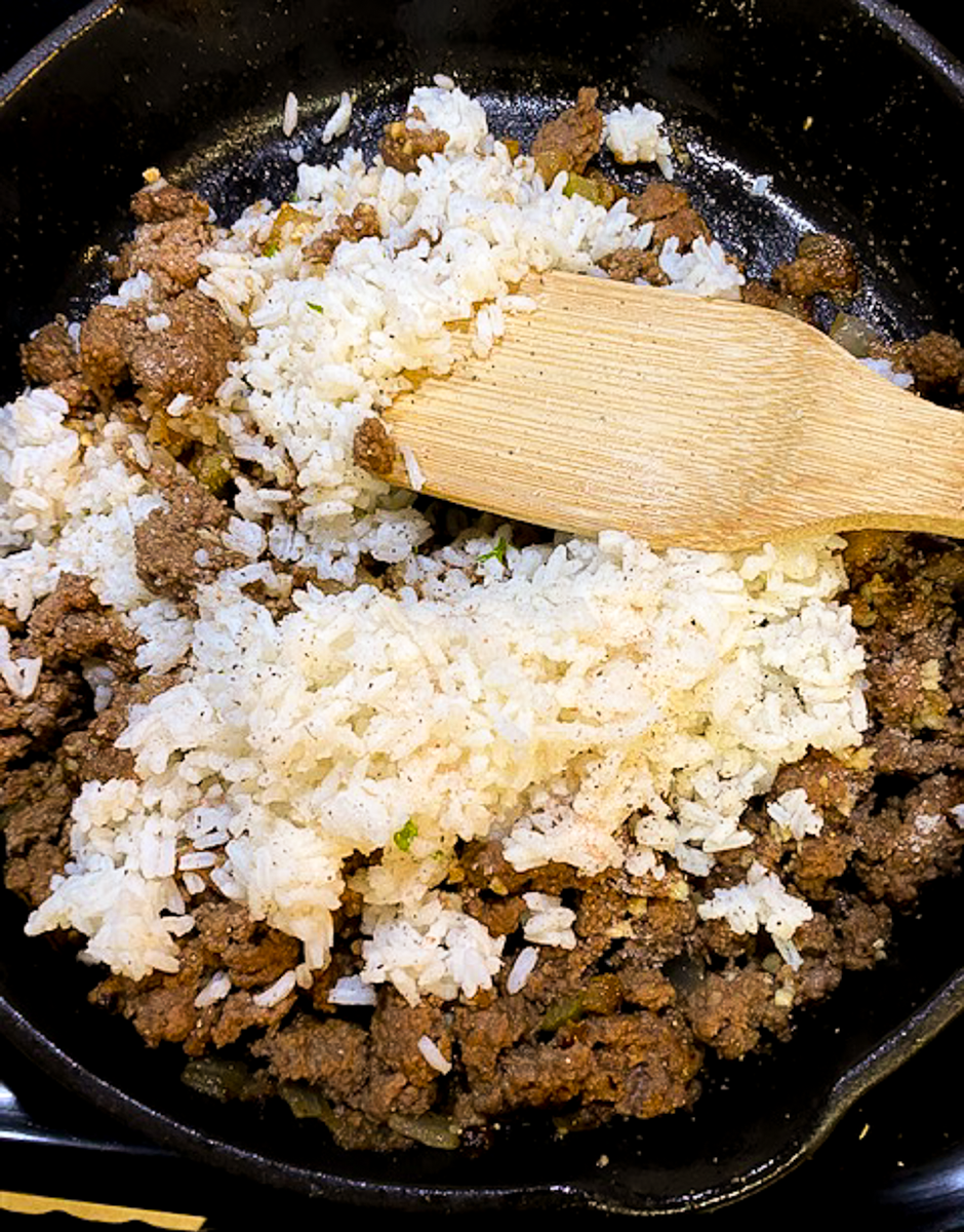 Cooked rice and seasoned ground beef in a skillet