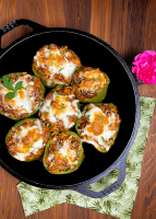 A round black iron skillet filled with Beef Stuffed Bell Peppers with Tomato Sauce against a brown wooden background.