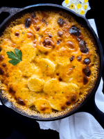 A black cast iron skillet filled with grain and gluten free potatoes au gratin.