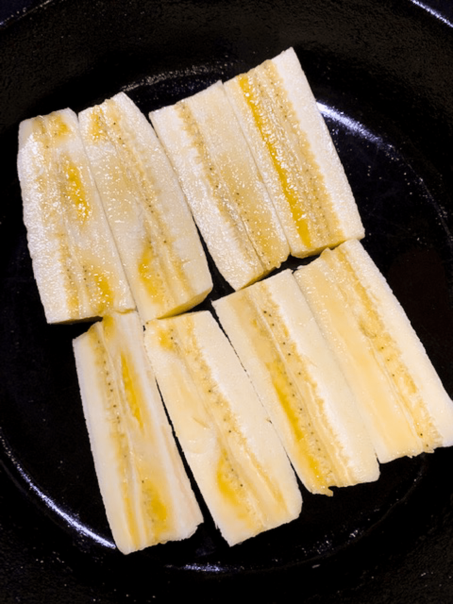 Cut bananas in a black cast iron skillet.