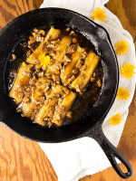 A black cast iron skillet filled with Baked Bananas Foster with pecans with a white napkin and yellow flowers against a wooden cutting board.