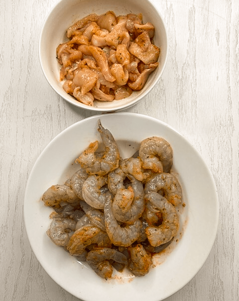 Seasoned shrimp and chicken in two bowls.