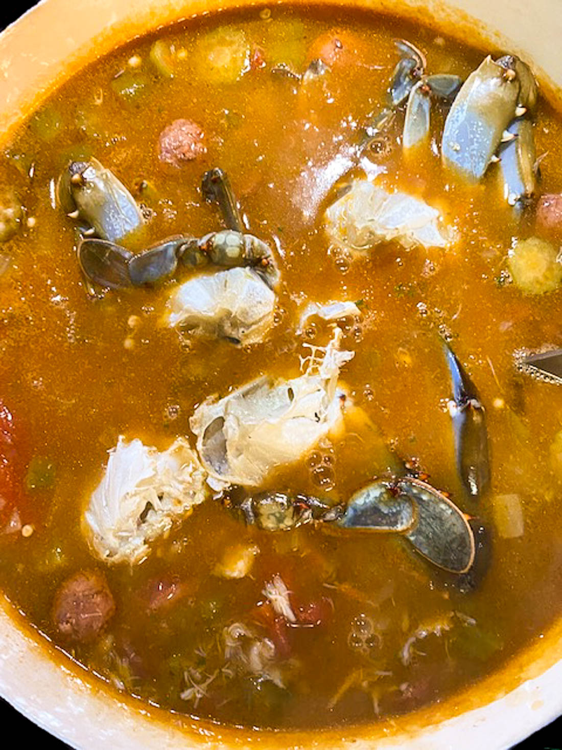Blue crabs being added to a pot full of Creole gumbo.