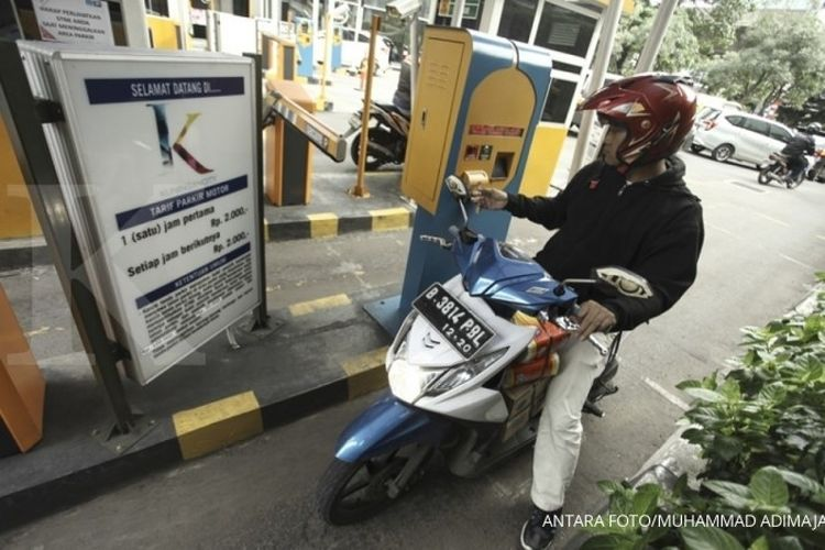 Pengendara sepeda motor mengambil tiket parkir di salah satu pusat perbelanjaan di Jakarta, Selasa (5/12).