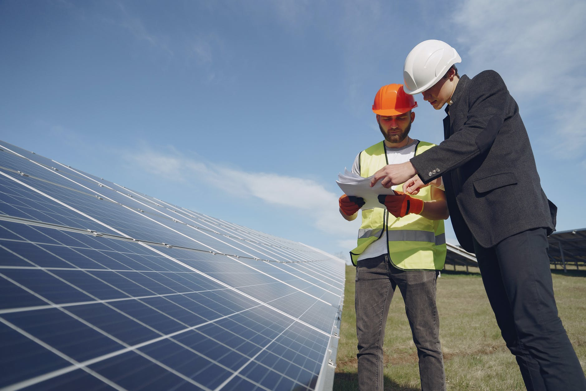 focused men with documents in hardhats at solar energy station