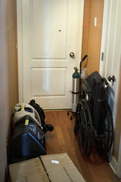 An oxygen tank and other medical equipment sit next to a door at a home in New Orleans.