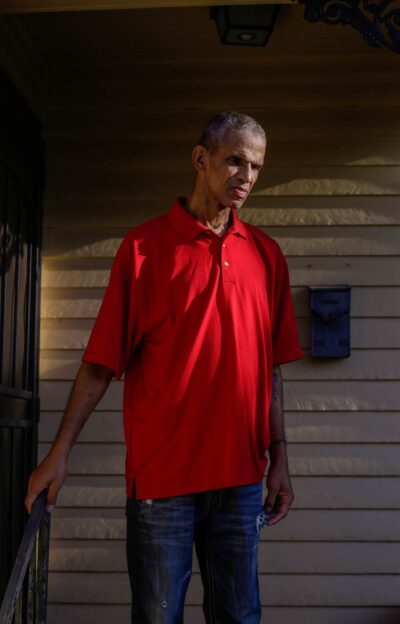 A man wearing a red shirt in quiet contemplation standing in front of his door.
