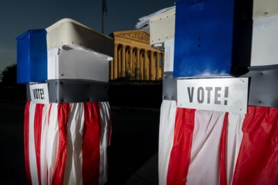Red white and blue prop ballot boxes in front of a Supreme Court building bathed in crepuscular light.