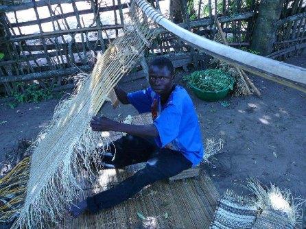 Hand weaving raffia to make Kuba cloth is men's work.