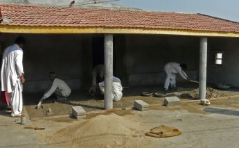 Laying cement for workshop shelter.
