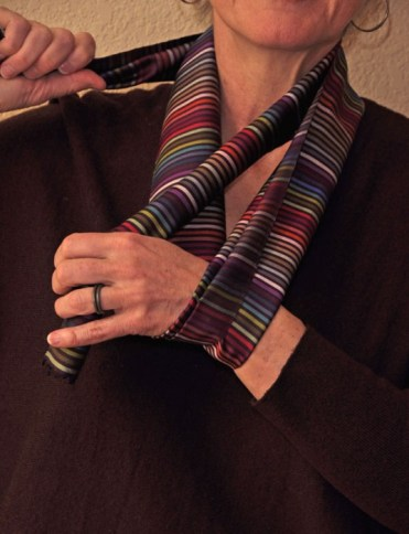 With your left hand still holding the short end, take your right hand and wrap the long end of the scarf around your neck. Let the scarf slide through your right hand but don't release it. The scarf is looped around your left hand and neck.