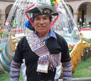 Leon Taipe Alayna from Huancavelica, Peru, dressed in finely knitted sleeves, crocheted scarf, and beaded hat.