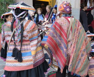 Two weavers from Pitumarca wear traditional ticlla (discontinuous warp) manta, worn by woman on left, and poncho, worn by man on right.
