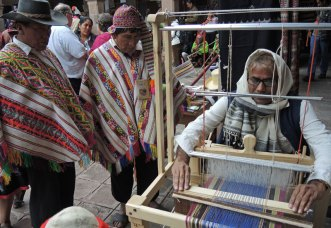 Indian artisan and designer, Dayalal Kudecha, demonstrates his traditional weaving while Peruvian weavers observe.