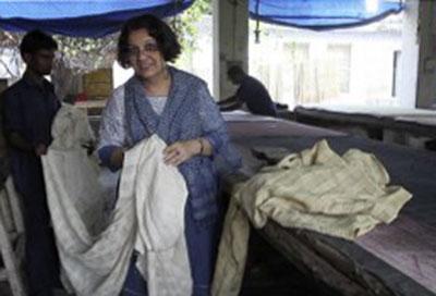 Bina with yards of handwoven window-pane silk fabric before dyeing.