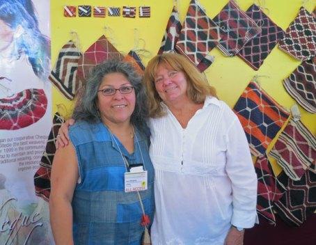 Ines Hinojosa and ClothRoads partner Linda Stark in front of Cheque Oitedie display at Folk Art Market.