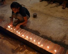 Candles being lit along the main route during the lantern festival in Luang Prabang, Laos.