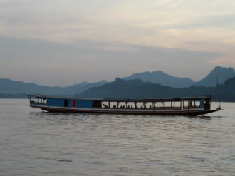 As night falls, travelers continue on their journey on the Mekong river in Laos.