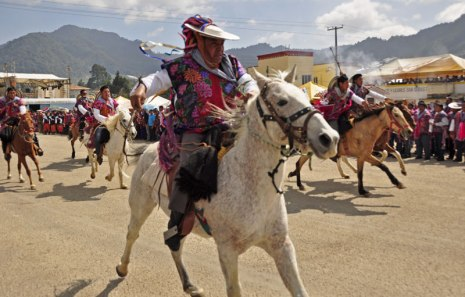 Zinacantan horsemen racing through plaza.