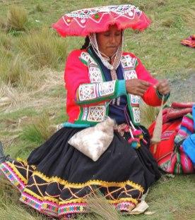 Handspinning alpaca. Her carrying bag is a manta.