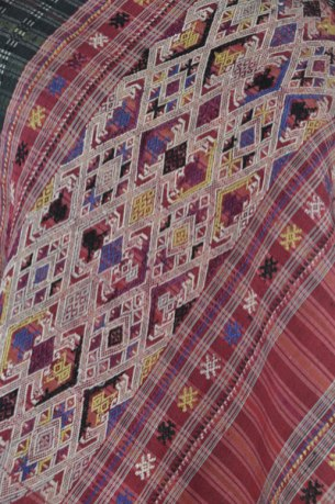 Intricate multicolored brocade patterns woven into silk shawl from Laos.