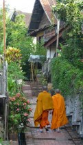 Monks walk along passageway in Luang Prabang, Laos