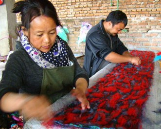 Laying out wool fibers over the sari fabric before the felting begins.