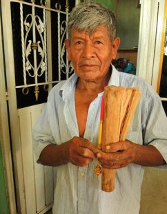 Antonio holds a finished spindle next to the mangrove root. He carves the spindle shaft from the root.