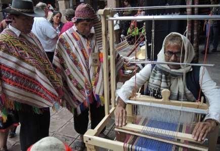 Dahyalal Kudecha demonstrates weaving to Peruvian men at weaving gathering in Peru.