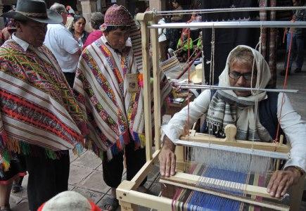 Dahyalal Kudecha demonstrates weaving to Peruvian men at weaving gathering in Peru.