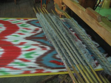 Ikat fabric being woven on the loom. The pattern is a multi-color warp resist-dye.