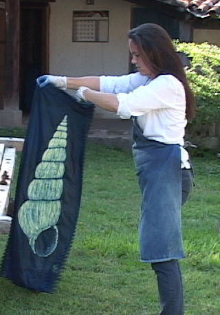 Grace Guirola with indigo dyed textile. Photo courtesy Mary Lance.