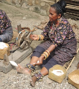 Traditional cotton spinning in Indonesia using a hand-cranked wheel and foot as spindle support.