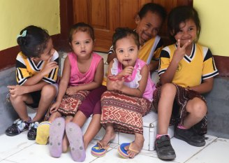 Children of the Amarasi tribe in west Timor Island wearing traditional ikat sarong skirts and school clothing.