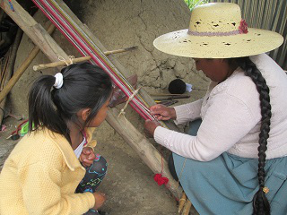 Doña Máxima weaves two yoga straps at the same time on her backstrap loom.