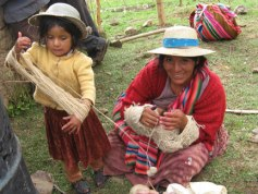 Ines from the Bolivian handspinning group, Warmis Phuskadoras, has a young helper wind her skein of handspun wool.