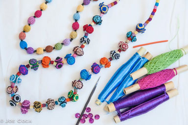 Rayon fiber on spool, a small, sharp pick, a narrow tube for holding the button while it's being made, and strong thread for threading the beads, and skillful hands of a master artisan=a necklace. Photo credit: Joe Coca