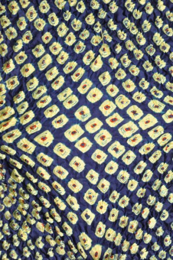 This fabric is stretched out so you can see the pattern formed by the tying of the bandhani pattern.