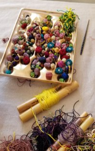 A tray of buttons made by the co-op members of Golden Buttons, along with rayon threads.