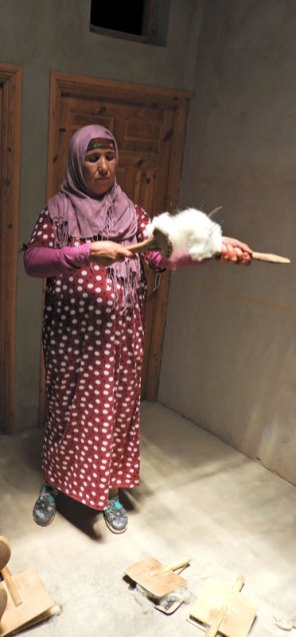 Fatima demonstrates wool carding.