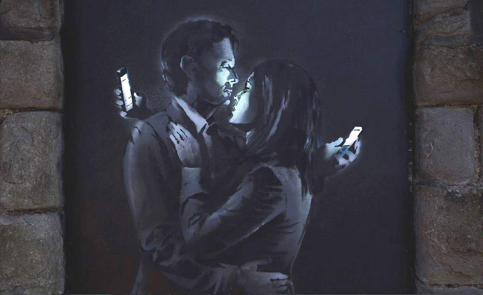Banksy piece of a man and a woman embracing while looking at their mobile phones.