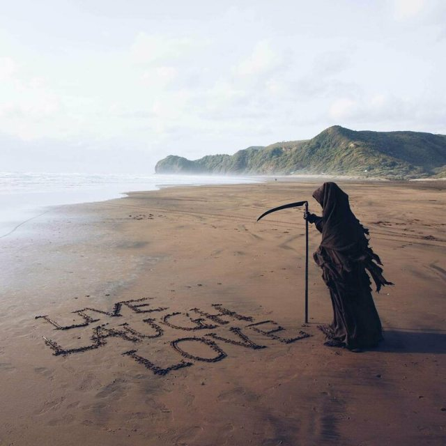 An ironic sand message from the Swim Reaper.
