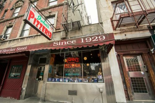 """John's Pizzeria in New York City. They advertise """"no slices"""" on the other side of their awning."""