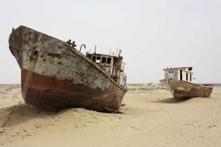 Two fishing vessels nestled in the sands near the former seaport city of Moynaq, Uzbekistan.