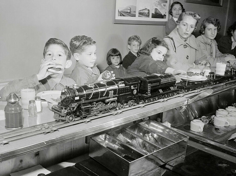 Children dive into train-delivered burgers at an early automated diner.