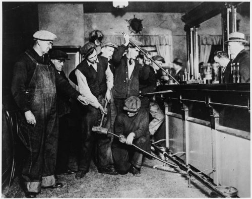 A group of Prohibition agents take crowbars to the bar.